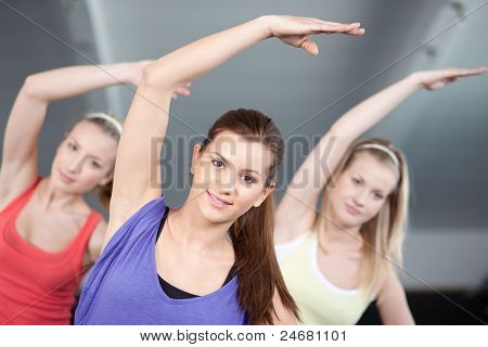 Close Up View Of Beautiful Young Women Stretching In A Health Club