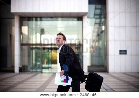 Fired Businessman About To Throw His Briefcase In Front Of An Office Building