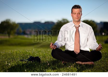 Businessman meditating outdoors to relieve stress. Against blue sky.