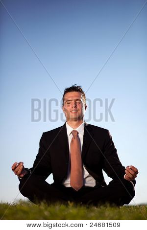 Businessman Meditating Outdoors To Relieve Stress