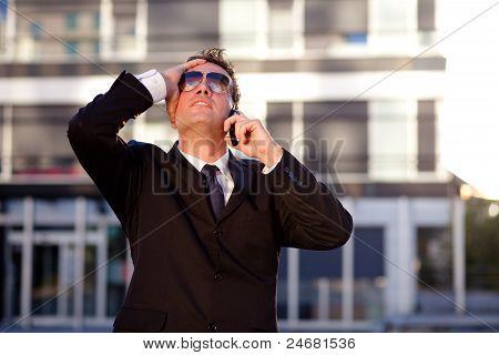 Jovem empresário moderno recebendo más notícias sobre o telefone. De pé na frente de um edifício de escritórios.