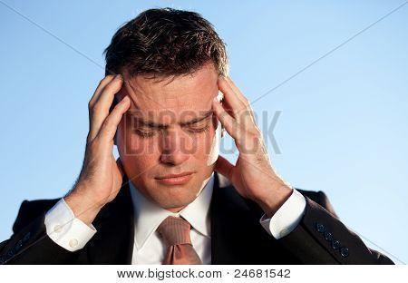 Businessman Under Stress Massaging His Head. Shot Against Blue Sky.