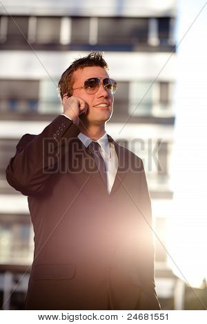 Modern Businessman Standing In Front Of An Office Building, Talking On The Phone