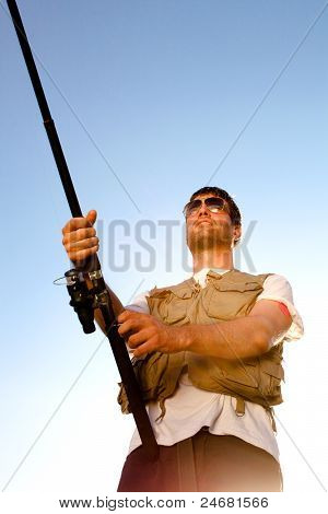 Fisherman against blue sky. The Fishing series.