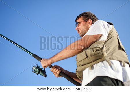 Fisherman Enjoying His Hobby. Shot Against Blue Sky.