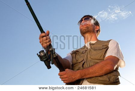 Man Fishing And Smoking A Cigarette. Shot Against Blue Sky.