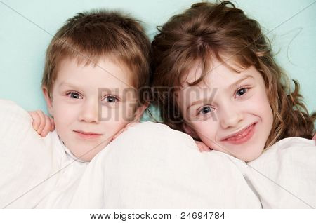 close-up portrait of two happy children in bed with bedclothes
