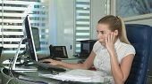 Portrait Of Young Unhappy Business Woman At Desk In Office poster