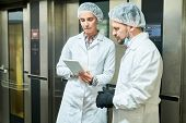 Confectionery Factor Workers Standing In White Coats Near Elevators And Using Tablet Computer. poster