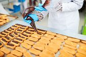 Crop Confectionery Factory Employee Decorating Pastry With Chocolate Cream Using Icing Bag. poster