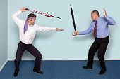Photo of two businessmen having a sword fight using umbrellas, good image to convey conflict, rivalr
