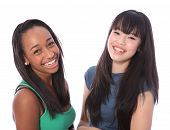 stock photo of laugh out loud  - Laughing out loud are two happy beautiful teenage friends a mixed race african american and oriental Japanese girls with big smiles and long black hair - JPG
