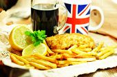 picture of flounder  - Traditional fish and chips with lemon and dark beer in newspaper wrapping - JPG