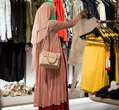Muslim Woman Choosing Clothes In Mall Or Clothing Store - Shopping, Fashion, Style And People Consum poster