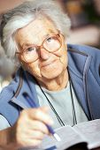 pic of elderly woman  - Portrait of an elderly woman solving crossword puzzle - JPG