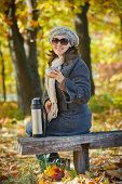 Woman drinks tea in autumn park