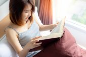 Attractive Beautiful Woman Is Reading Novel Book On Bed Near Window At Bedroom That Make Her Get Goo poster