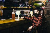 Rest And Relax Concept. Guy Spend Leisure In Bar, Defocused Background. Man With Strict Face Sit In  poster