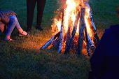 People Around Bonfire Burning Bright In Dark On Green Grass Field At Midsummer Night. poster