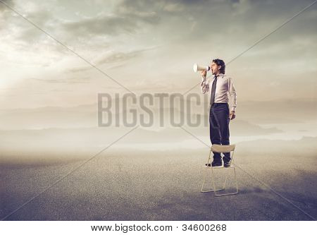 Businessman standing on a chair and screaming into a megaphone in a desert