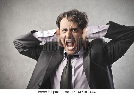 Disgusted businessman shutting his ears with his hands