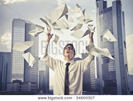 Young businessman throwing some paper sheets in the air with cityscape in the background