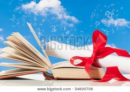Abschluss durch Bildung mit Blättern und Buch gegen blauen Himmel