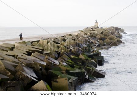 Fishermen And Walkers In The Breakwater