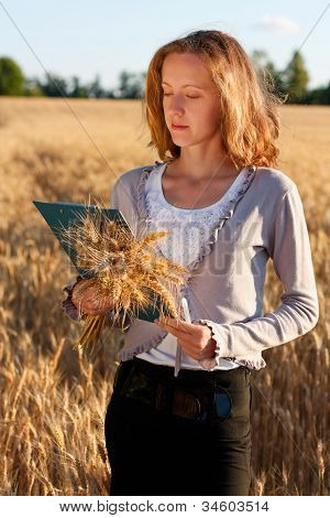 Woman Agronomist With Document Analyzing Wheat Ears