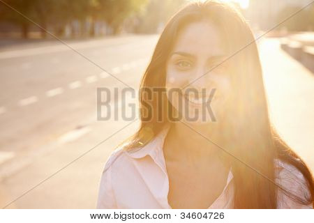 Beautiful lady in sunset light walking along the street
