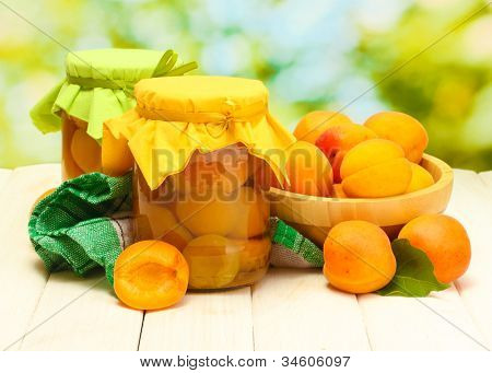 canned apricots in a jars and ripe apricots in bowl on wooden table on green background