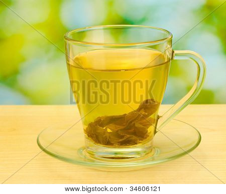 green tea in cup on wooden table in garden