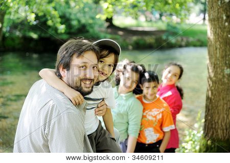 Happy father and  children together outdoor, faces, smiling and careless
