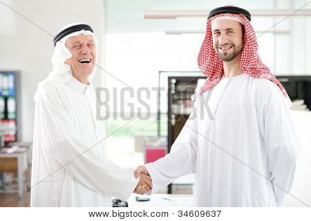 Successful Arabic business people shaking hands over a deal in office