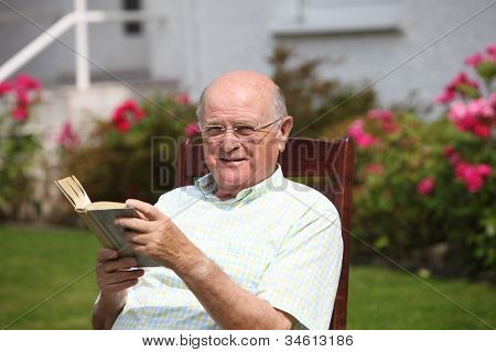 Elderly Man Reading A Book In Sunshine