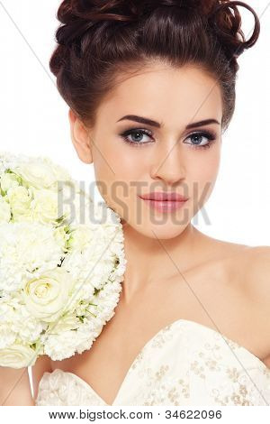 Portrait of young beautiful bride with stylish make-up and hairdo over white background
