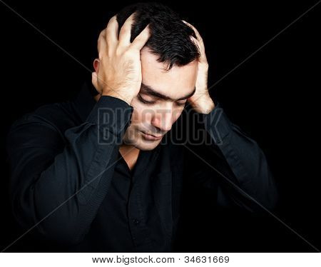 Classic portrait of an hispanic man suffering a strong headache or depression pressing his forehead with his hands isolated on black