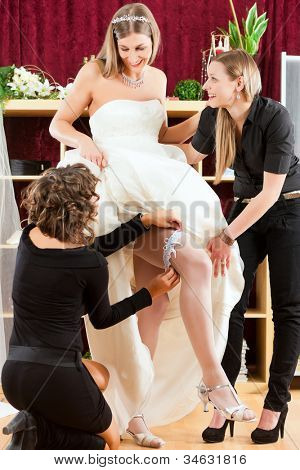 Bride at the clothes shop for wedding dresses, she is choosing a dress and wears a garter