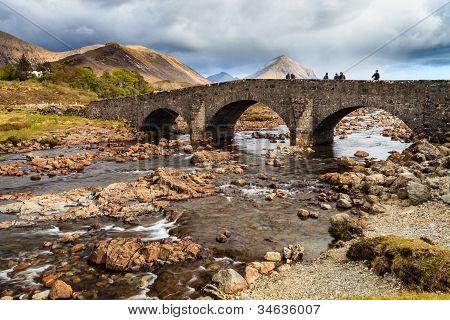 Gente de pie en un puente sobre un río