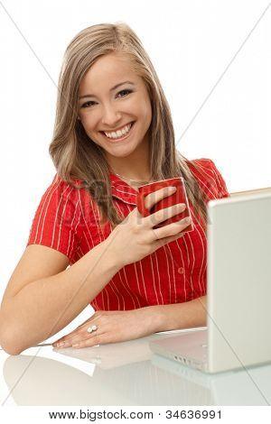 Beautiful blonde woman drinking tea, using laptop computer, smling.