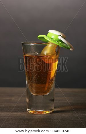 Baby dummy with alcoholic beverage on grey background