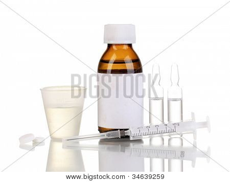 Medical bottle with jigger, tablets, ampoules and syringe isolated on white