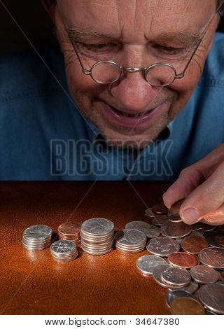 Senior Man Counting Cash Into Piles