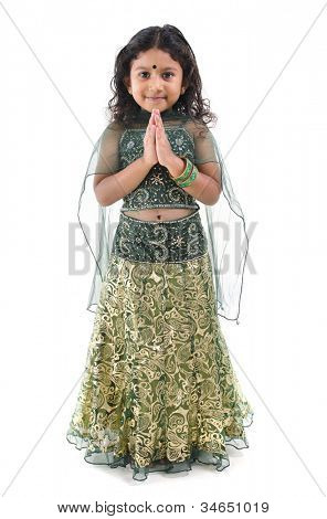 Cute little Indian girl in a greeting pose, isolated white background