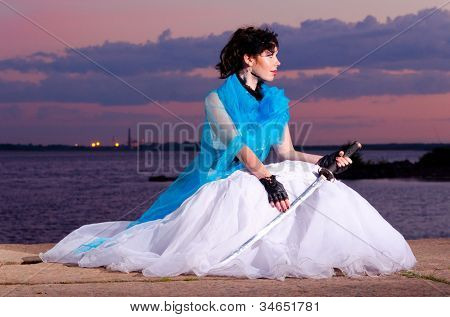 young woman in wedding dress at sunset