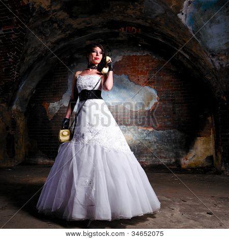 mujer joven en vestidos de novia en lugar abandonado