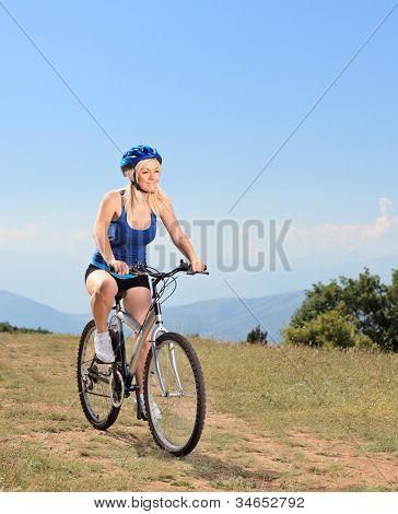 A female biker biking a mountain bike on a sunny day