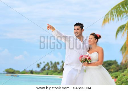 A bride with a bouquet of flowers and groom looking towards, shot on a beach in Kuredu resort, Maldives island, Lhaviyani atoll