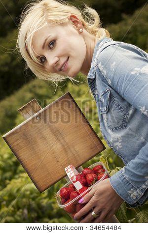 schöne blonde Frau pflücken Erdbeeren