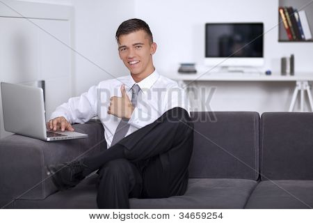 Young Businessman Showing Hand Gesture Thumb Up Success Sign Sitting On Couch